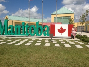 Eventually, Choppy and I made it to Canada - Choppy's first foreign country! One of the ladies at the not-terribly-busy travel information center was kind enough to come outside and take a picture of Choppy and me in front of the Canadian flag and Manitoba sign to document this occasion.